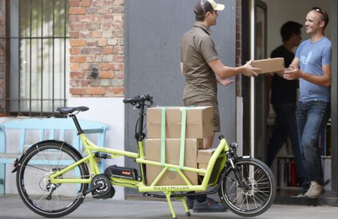 A UPS employee using a Bakfiets cargobike from Riese & Muller.