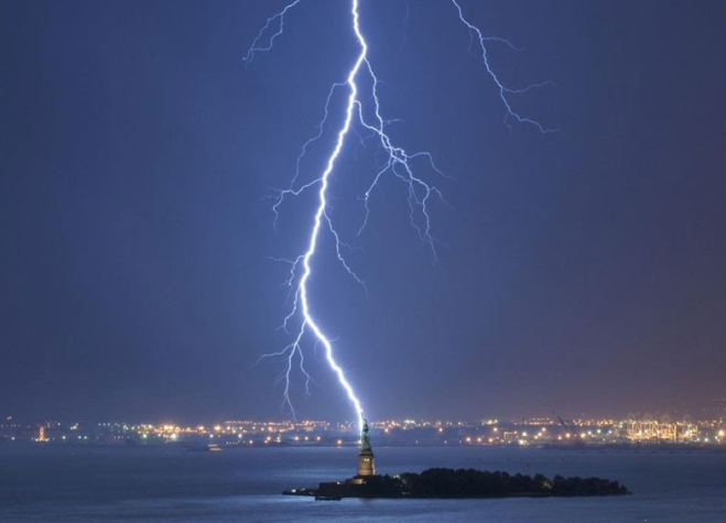 Lightning strikes the Statue of Liberty.